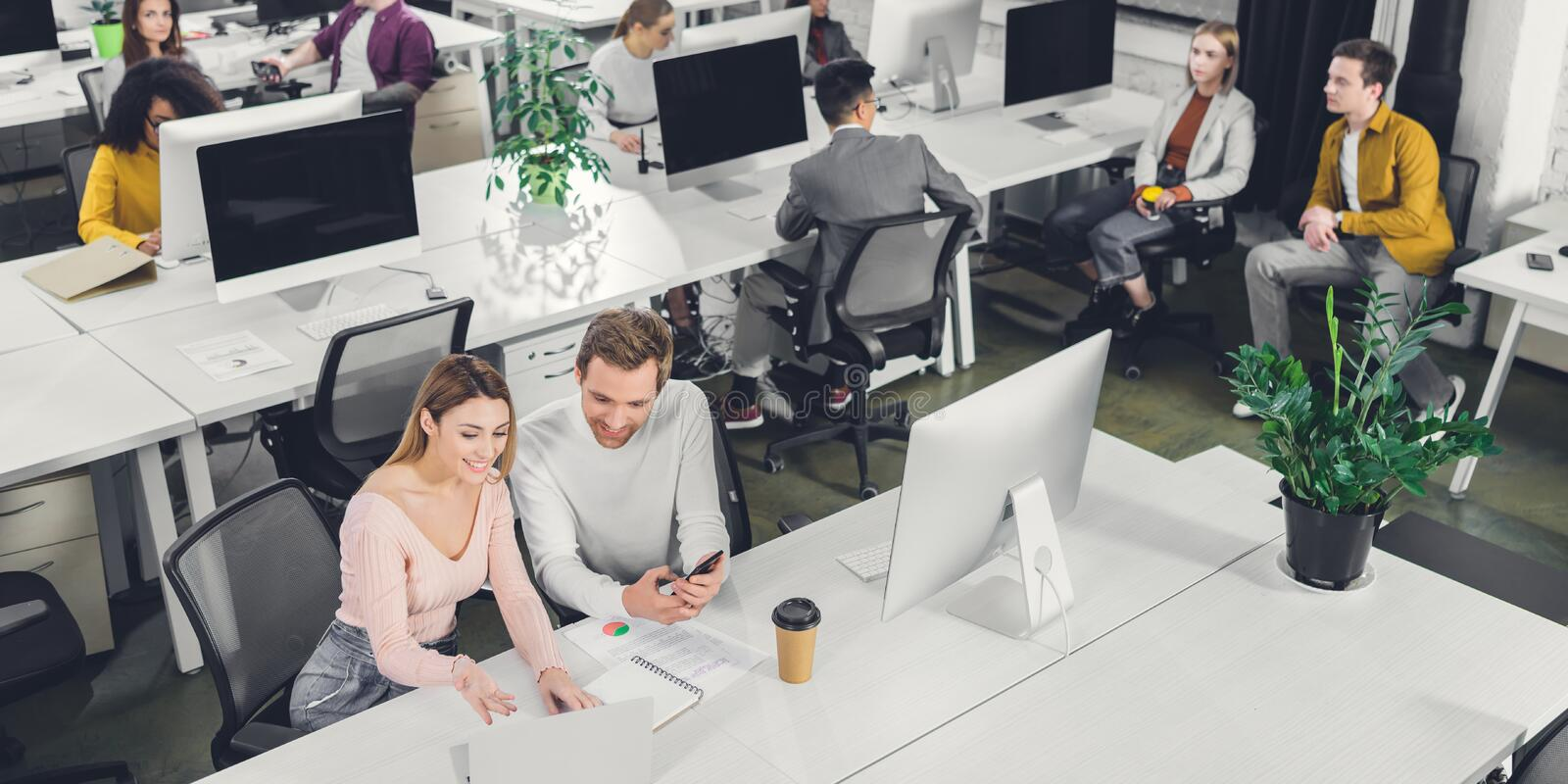 High angle view of smiling young businessman and businesswoman talking while working with colleagues stock photography
