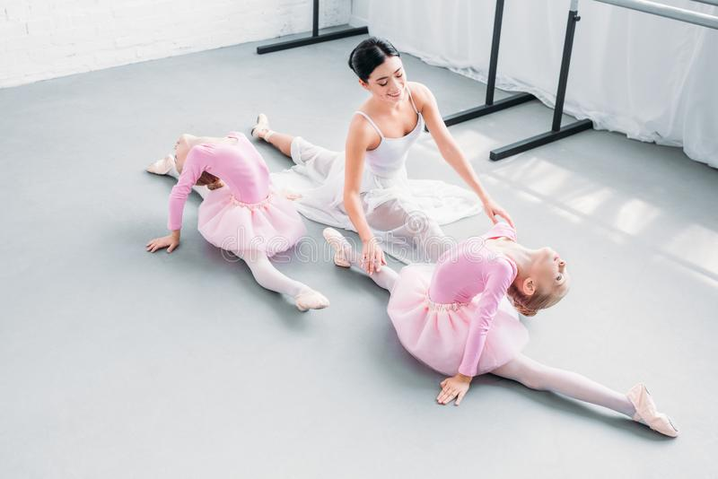 high angle view of smiling young teacher with cute little ballerinas exercising royalty free stock image