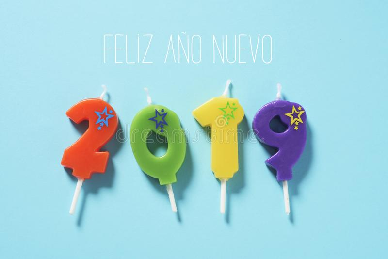 Text happy new year 2019 in spanish. High angle view of some number-shaped candles of different colors forming the number 2019, and the text feliz ano nuevo stock photography