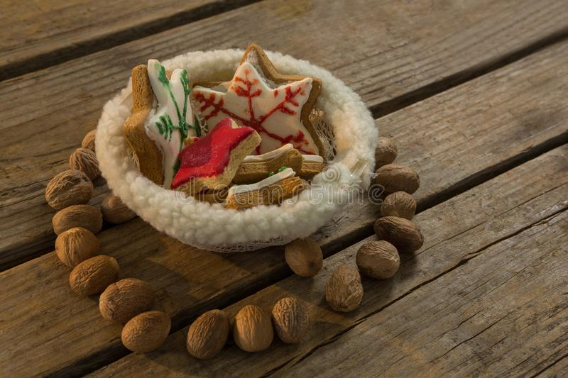 High angle view of star shape cookies in bowl amidst walnuts. On wooden table stock image