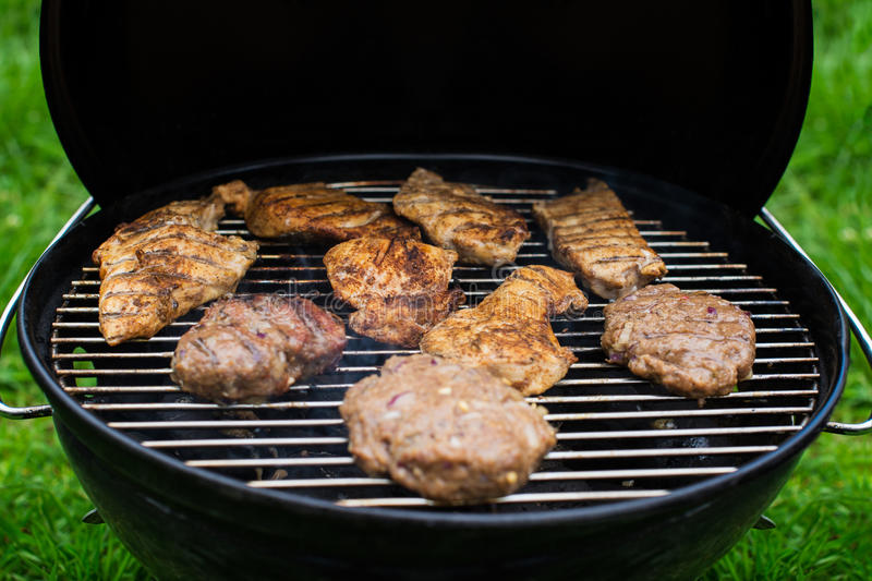 High angle view of succulent steaks and burgers cooking on a barbecue over the hot coals on a green lawn outdoors. royalty free stock photos