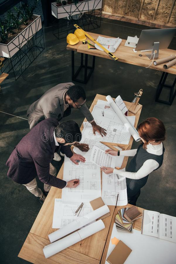 high angle view of team of architects working with architectural plans royalty free stock photo