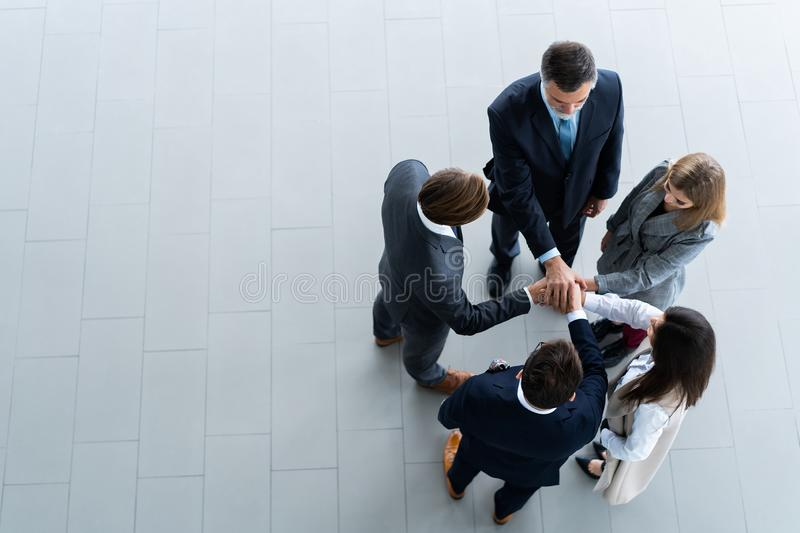High angle view of a team of united coworkers standing with their hands together in a huddle in the modern office royalty free stock photography