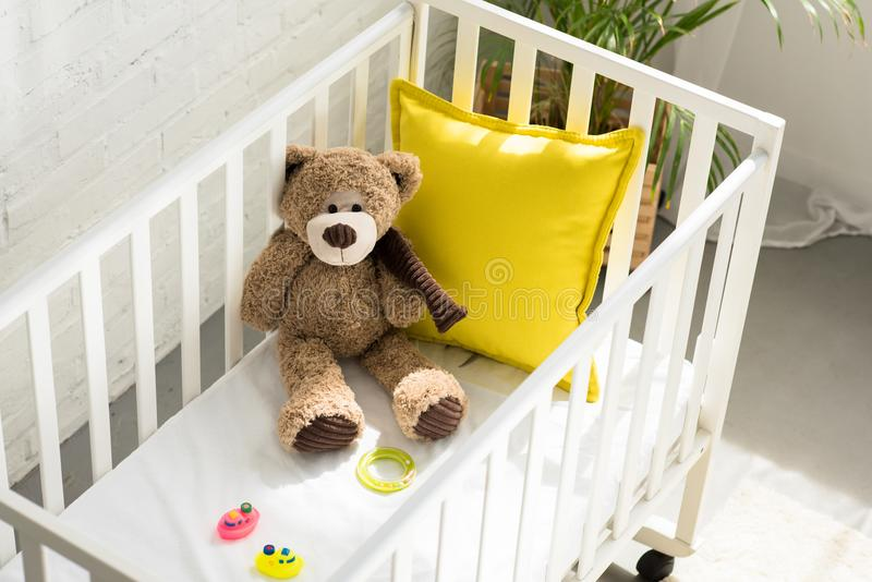high angle view of teddy bear, other toys and yellow pillow in baby crib royalty free stock photography