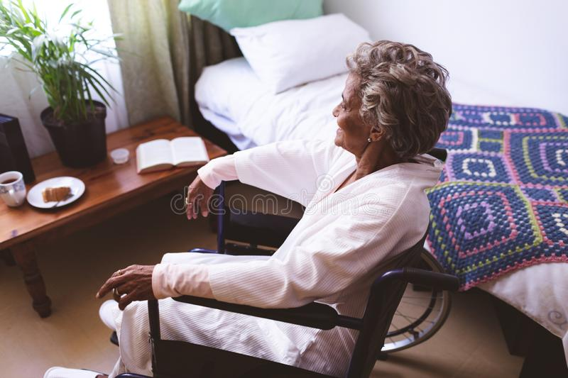 Thoughtful senior woman sitting on wheelchair at nursing home stock images
