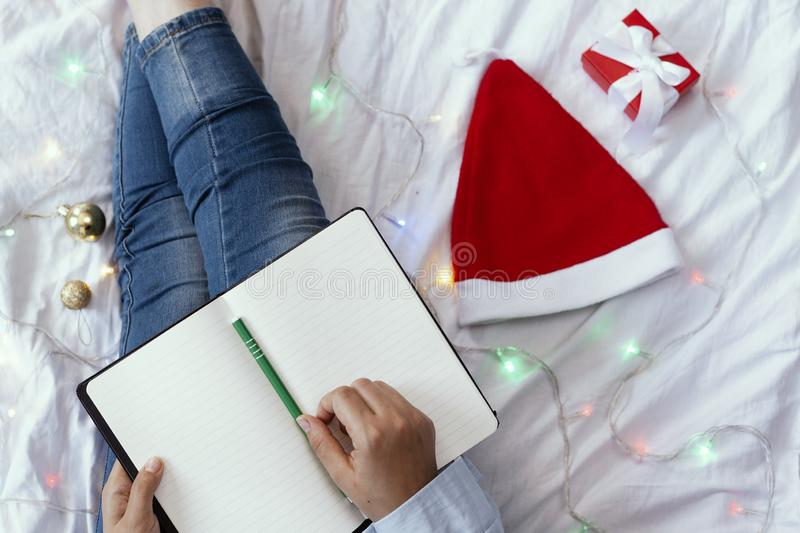 High angle view to young woman lying in bed and writing with pen on notebook. Wintertime. Christmas holidays. A woman making plans. For the new year. New year royalty free stock photo