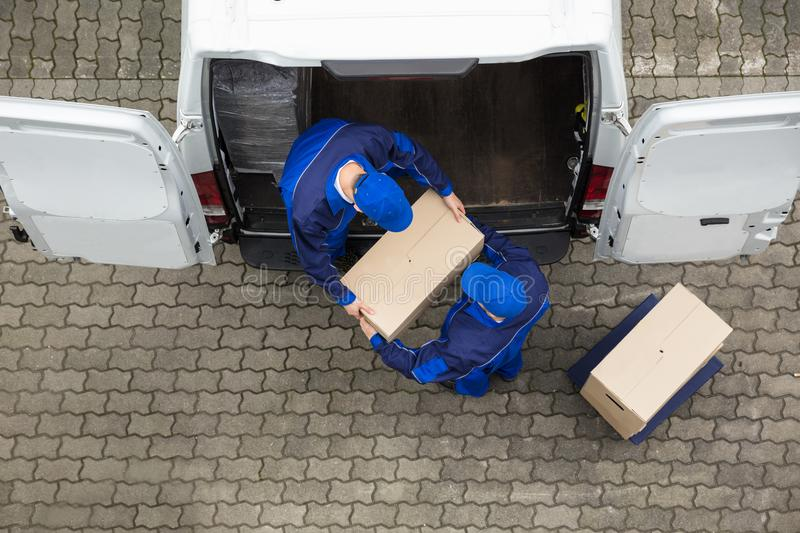 Two Delivery Men Unloading Cardboard Box From Truck. High Angle View Of Two Delivery Men Unloading Cardboard Box From Truck royalty free stock image