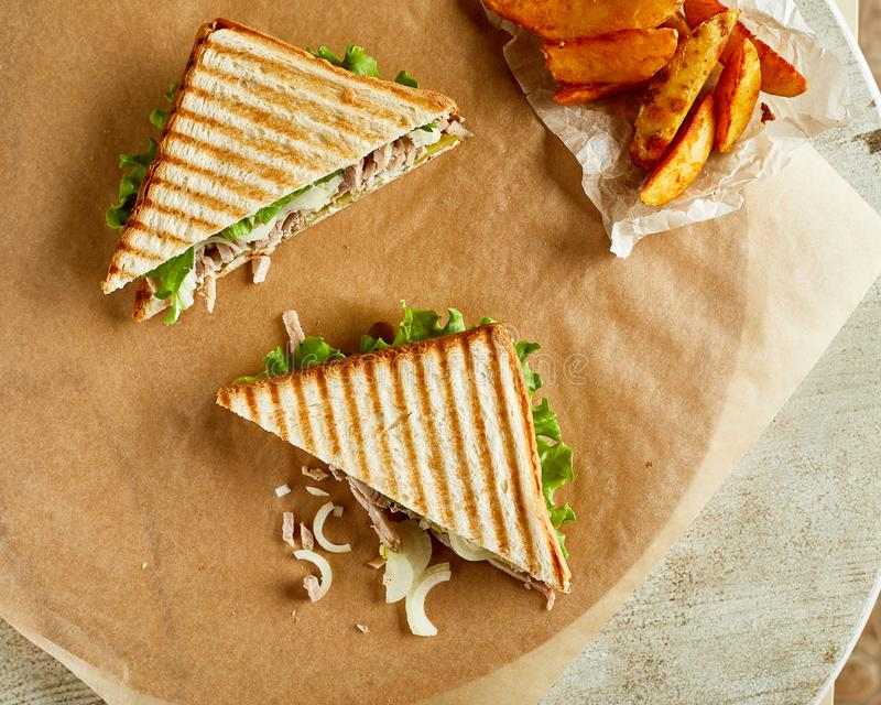 Two grilled sandwiches, served on backing paper with fried crisp. High angle view of two grilled sandwiches, served on backing paper with fried crispy potato stock photo