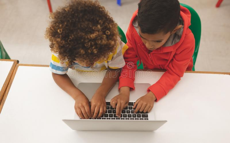 High angle view of two mixed-race school boys taping on the keyboard of their laptop royalty free stock image