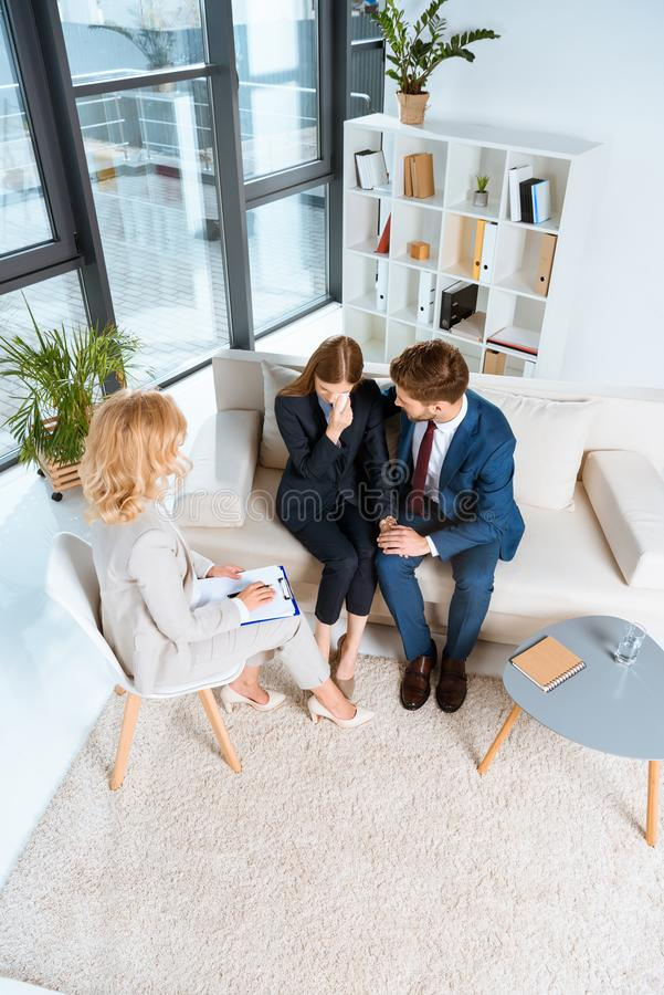 high angle view of upset young couple and psychologist sitting together stock images