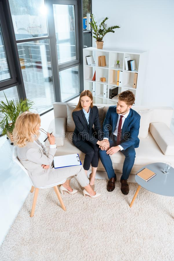 high angle view of upset young couple talking with psychologist royalty free stock image