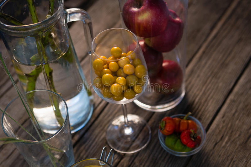 High angle view of winter cherry and apples in container. On wooden table stock photo