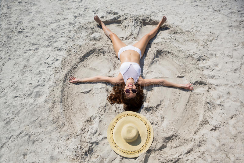 High angle view of woman making sand angel at beach stock image