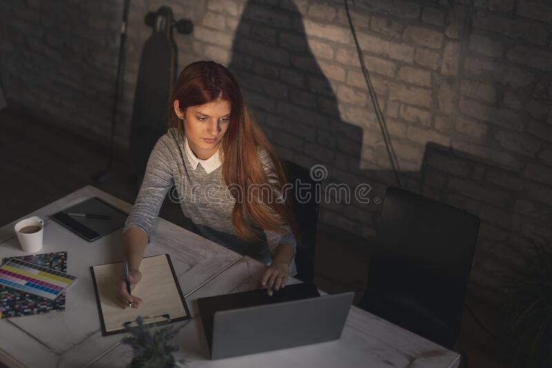 Woman telecommuting. High angle view of woman telecommuting, working on a laptop computer and taking notes in a planner stock image