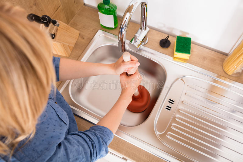 High Angle View Of Woman Using Plunger In Sink. High Angle View Of Woman Using Plunger In Blocked Kitchen Sink To Unclog Drain stock photography