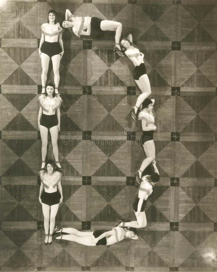 High angle view of women forming the letter D
