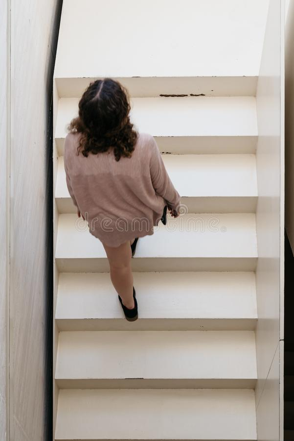 High angle view of young adult woman moving up modern architectu stock photo