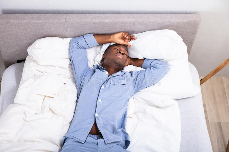 High Angle View Of Man Sleeping On Bed stock images