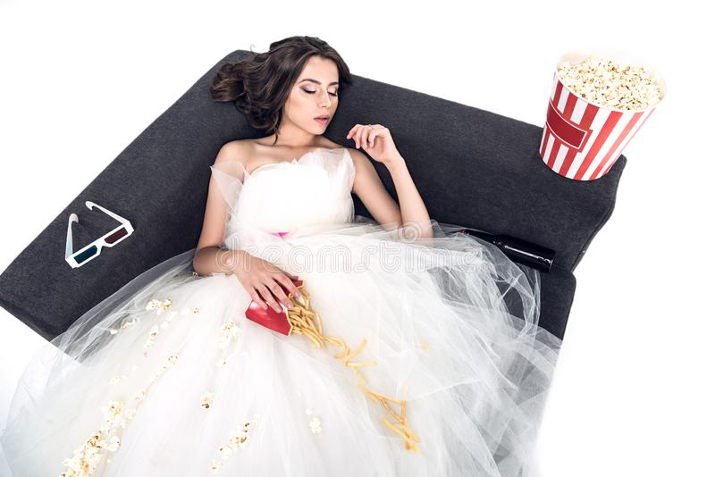 high angle view of young bride in wedding dress sleeping on couch with junk food stock photography