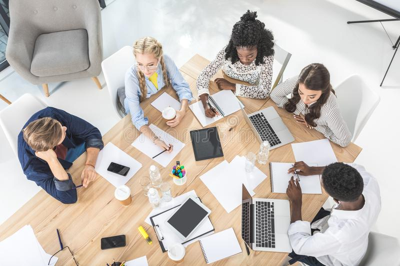 high angle view of young business team discussing business plan during conference stock images