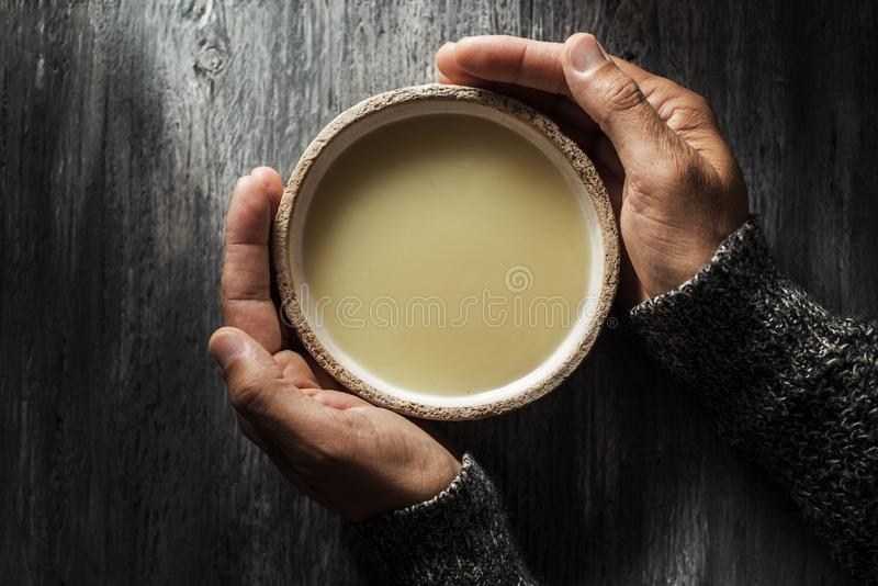 Man warming up with a bowl of hot soup. High angle view of a young caucasian man warming up with a bowl of hot soup, on a gray rustic wooden table royalty free stock images