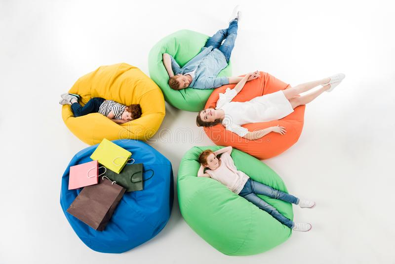 high angle view of young family with two kids resting on bean bag chairs after shopping stock image