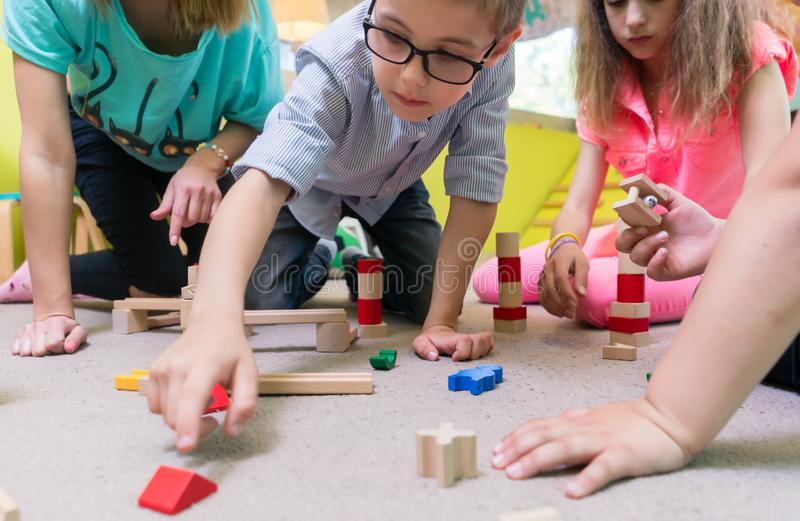 Female educator teaching children to build a train circuit durin. High-angle view of a young female educator teaching children to build with patience a wooden stock photos