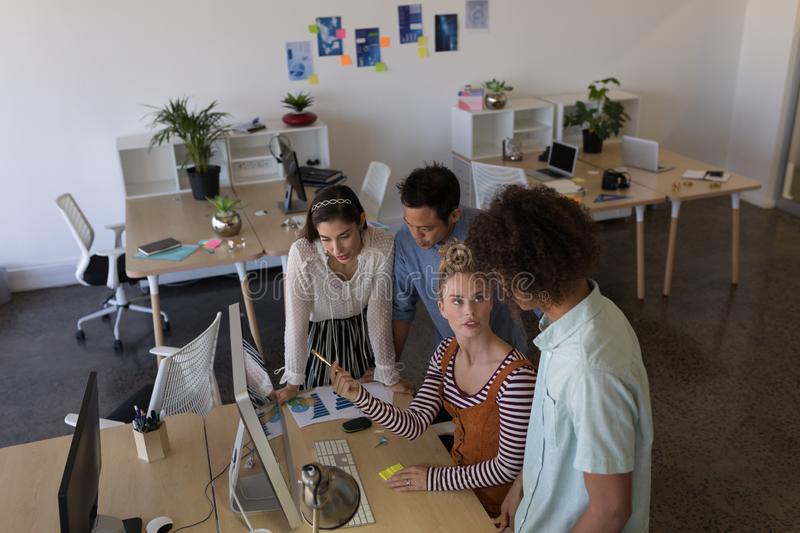 Business colleagues discussing over desktop pc in office royalty free stock photo