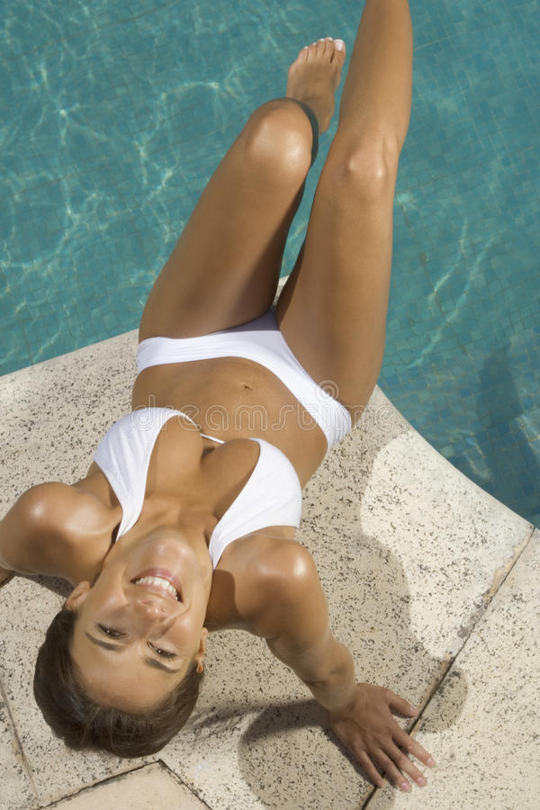 High angle view of a young woman sitting at the poolside stock images