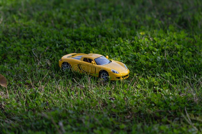 High angle zoomed close up shot of one yellow toy car on grass in the garden during sunrise and light rays falling on it. A toy car placed in filtering sunlight stock images