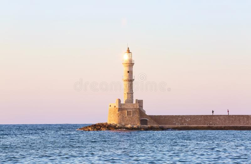 High, beautiful, ancient lighthouse made of bricks. Marvelous sunset lights the sky. Touristic resort Chania, Greece. High, beautiful, ancient lighthouse made stock photography
