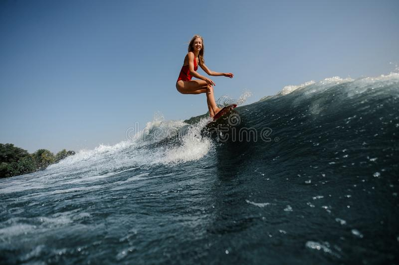High blue wave on a foreground and beautiful blonde woman wakesurfing on board. On the background stock photo