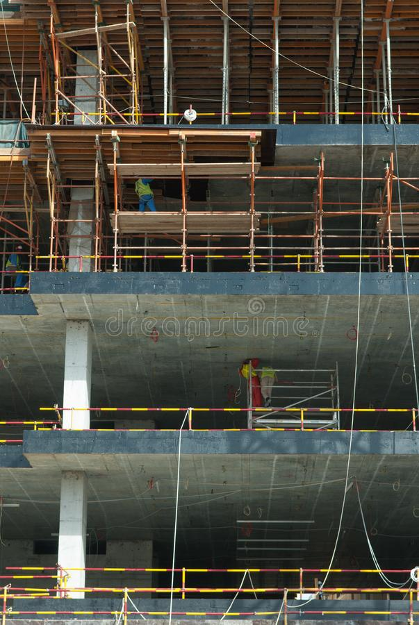 Multi-story building construction site with workers on scaffolds stock photos