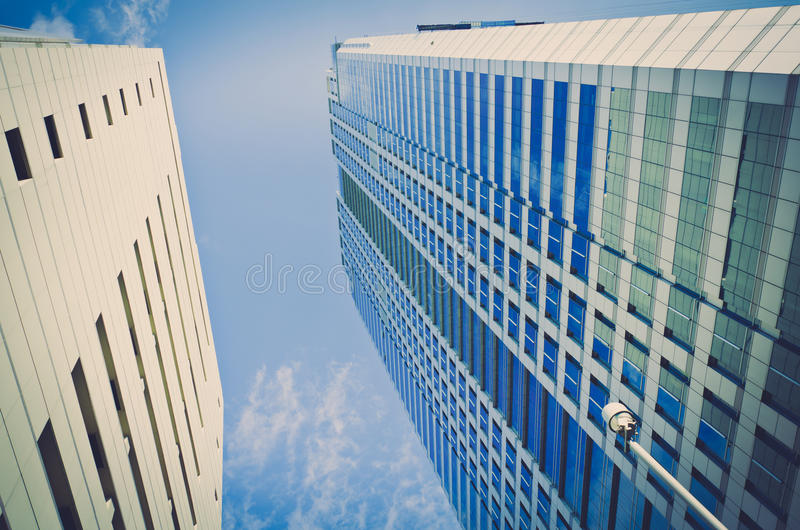 A high building skyscraper construction in the blue sky. In vintage retro color for office and real estate business stock photo