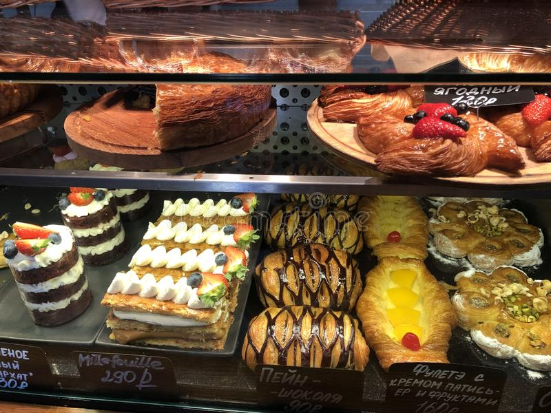 Variety of high-calorie delicious desserts lying on the bakery window stock image