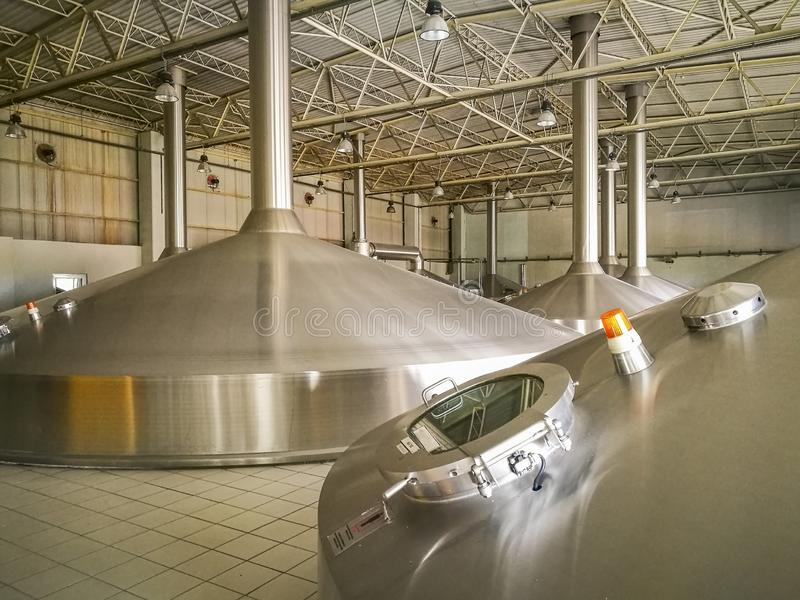 Beer storage reservoirs of a brewery. High capacity aluminum reservoirs of a brewery in first stage of beer production process when ingredients are boiled and stock photography