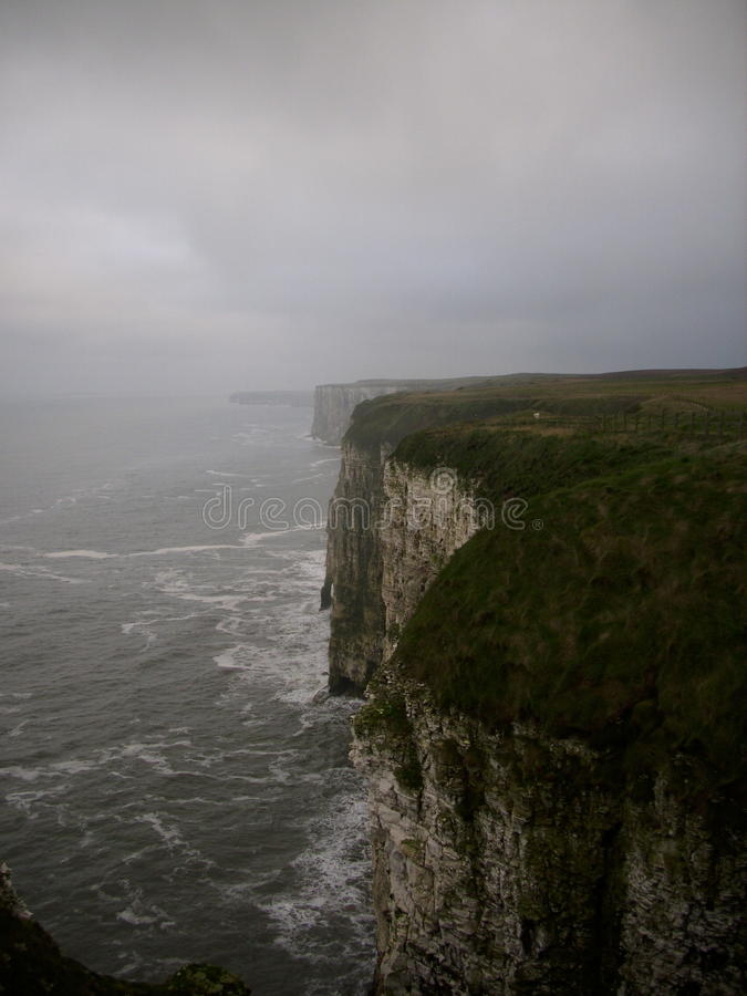 Chalk cliffs with sea spray. High chalk cliffs with sea and mist. Grey sky as background royalty free stock image