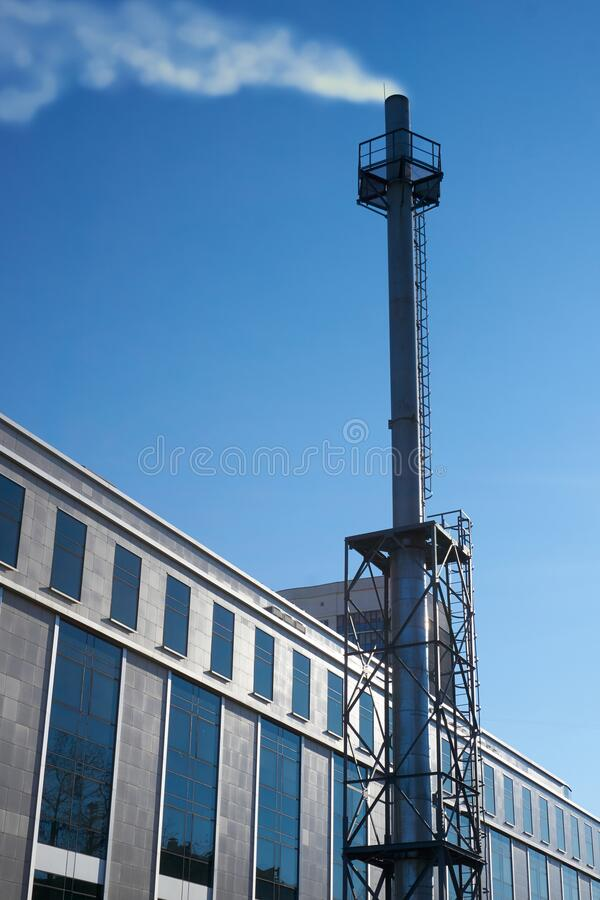 High chimney made of stainless steel of an industrial gas boiler with smoke coming out of it steam. Building with autonomous. High chimney made of stainless stock photo