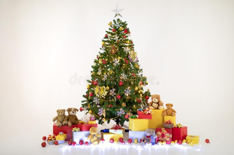 Pile of Christmas ornaments and high tree with lights. royalty free stock photography
