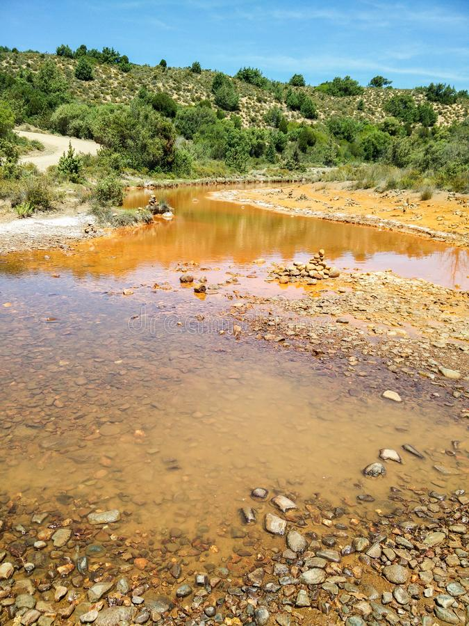 Environmental pollution. Water. High concentrations of heavy metals determines the orange-red color of waters and sediments of the Rio Piscinas in the Arburese royalty free stock photos