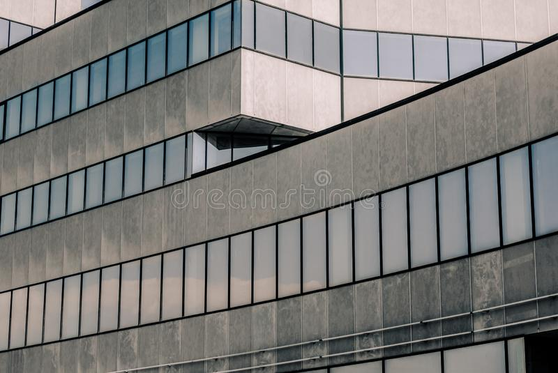 Gray high concrete building with reflection of the sky and clouds in the windows royalty free stock photos