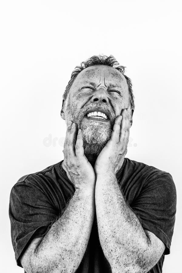 High contrast black and white portrait of a man with beard in pain stock photography