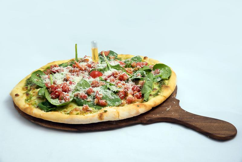 `A high contrast Hero shot of a Bruschetta Al Pesto Spinaci Pizza, on a minimal white background with a 30 degree angle from zoome. D out lateral perspective stock photo