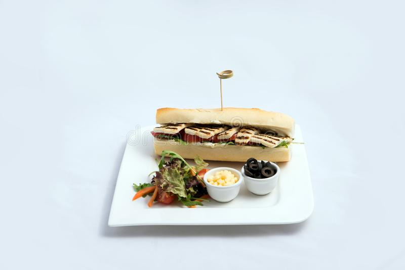 A high contrast Hero shot of a Grilled Halloumi cheese baguette with olives & salad on the side, on a minimal white background royalty free stock image