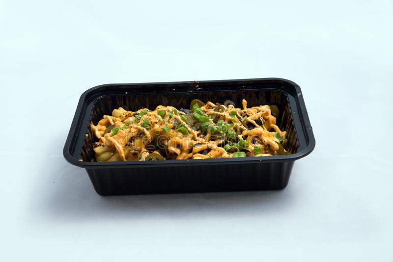 A high contrast Hero shot of a Take-Away Hot Loaded fries / chips with cheese, ground meat, olives, jalapeno, sauce & oregano, on stock photos