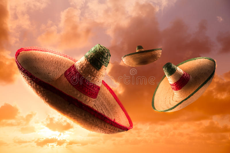 High contrast image of Mexican hats / sombreros in the sky. Mexican sombreros in a dramatic orange sky stock photos
