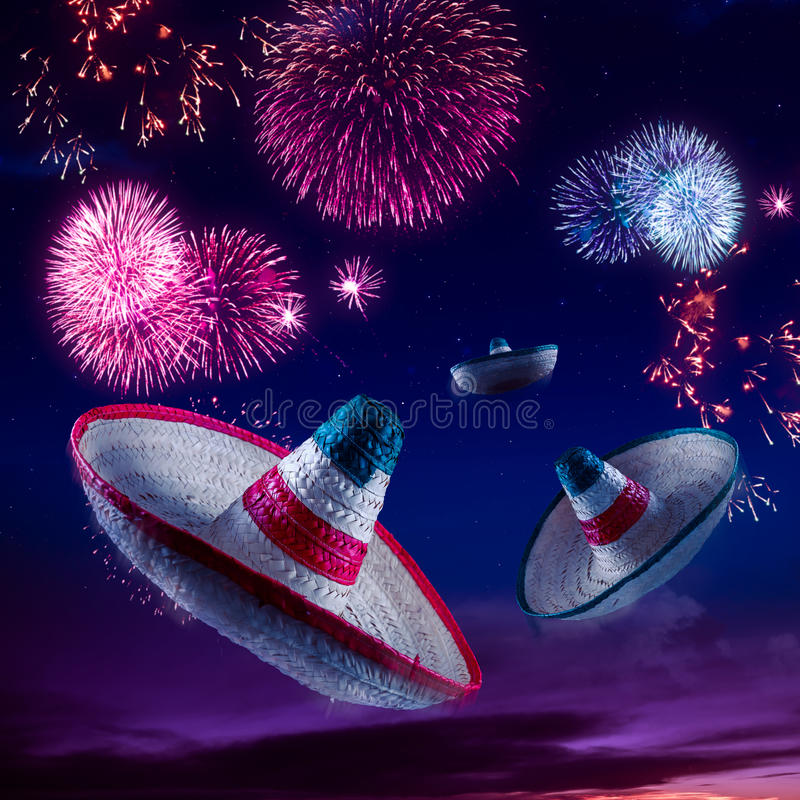 High contrast image of Mexican hats / sombreros in the sky with. Mexican sombreros with fireworks at night royalty free stock photo