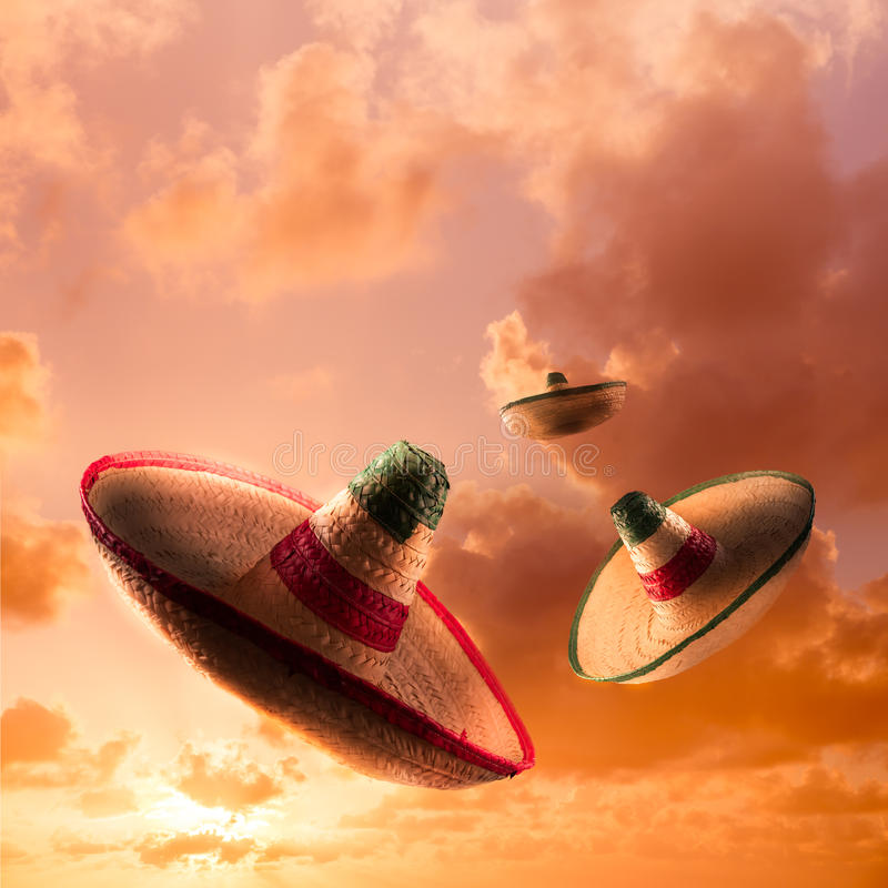 High contrast image of Mexican hats / sombreros in the sky, square format. Square format image of Mexican sombreros in a dramatic orange sky royalty free stock photography