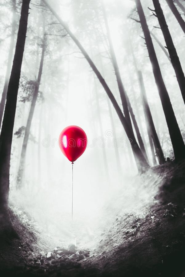 High contrast image of a red balloon in the woods royalty free stock photo