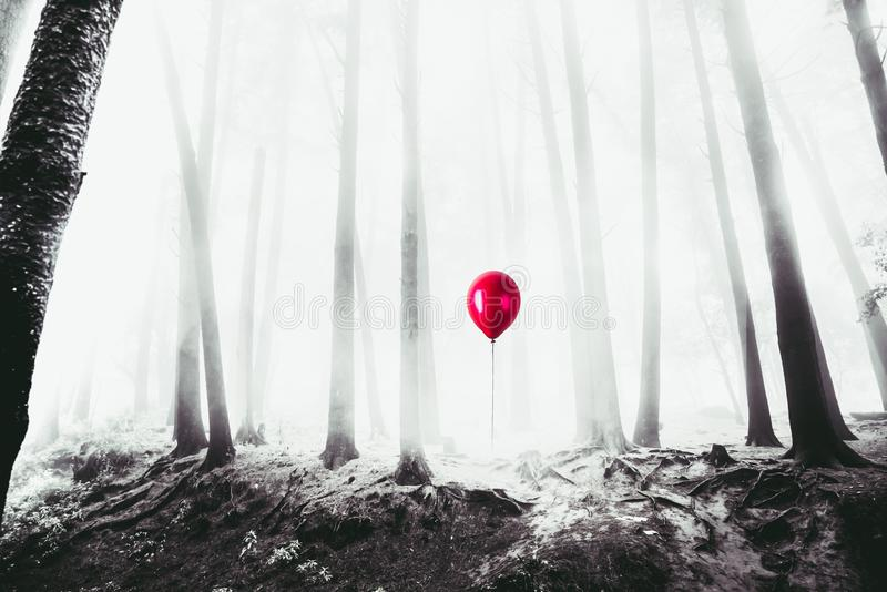 High contrast image of a red balloon in the woods stock photo